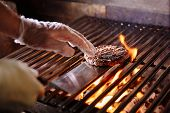 Chef Making Burger. Beef Or Pork Meat Barbecue Burgers For Hamburger Prepared Grilled On Bbq Fire Fl poster