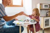 Father and daughter having a tea party at home  poster