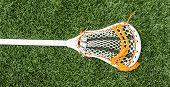 A White Lacrosse Stick With Some Orange Trim On Green Turf. poster