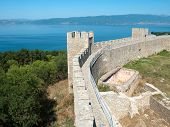 walls and towers embattled of castle Samuil, on background the blu waters of Ohrid lake, Republic O