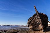 Old traditional Tagus River wooden sailboat burnt and wrecked in Seixal Bay, Portugal poster