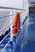 Bright Lifebuoy With Light Hanging On The Ship On A Cloudy Day Against The Open Sea. poster