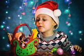 A Cute Boy In A Hat Santas Looks At A Gift. Candy Christmas Sleigh. Little Cute Boy With Santa Hat. poster