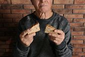 Poor Elderly Man With Bread Near Brick Wall, Closeup poster