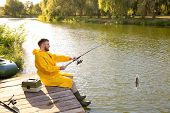 Man With Rod Fishing On Wooden Pier At Riverside. Recreational Activity poster