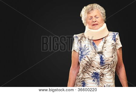 A Senior Woman Wearing A Neck brace On Black Background