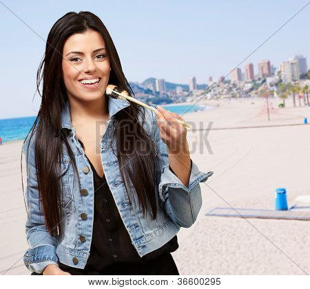 Young Woman Holding A Piece Of Sushi With Chopsticks, Outdoor