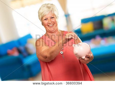 Woman Putting Coin In Piggy Bank, Indoor