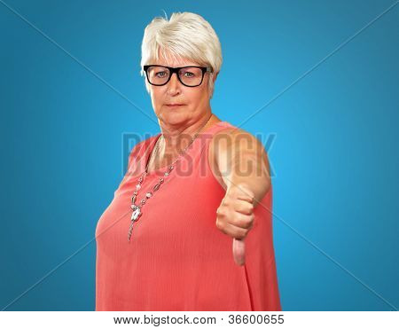 Senior Woman With Thumbs Down Isolated On Blue Background