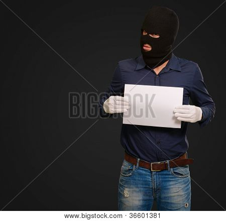 Man wearing a robber mask showing a blank paper on black background