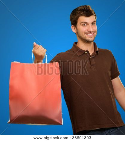 Portrait Of A Young Man Holding A Handbag On A Blue Background