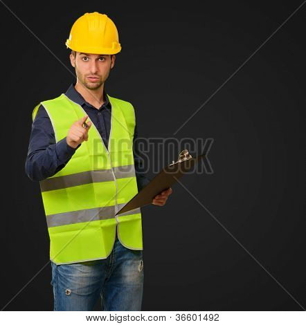 A Young Engineer Holding A Writing Pad On Black Background