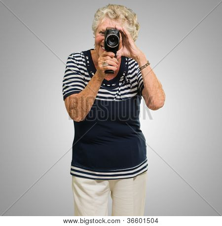 Portrait Of Senior Woman Looking Through Video Camera Isolated Over Gray Background