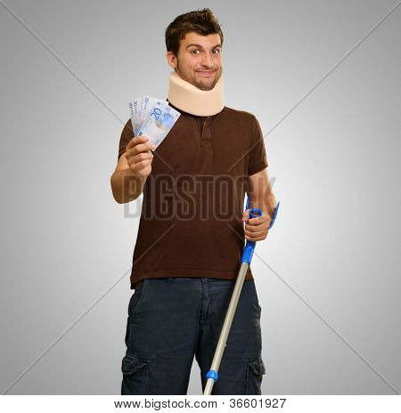 Young Man With Crutches Holding Note On Gray Background