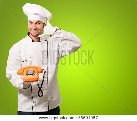 Portrait Of A Chef Holding A Telephone On Green Background