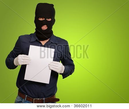 Man wearing a robber mask showing a blank paper on green background