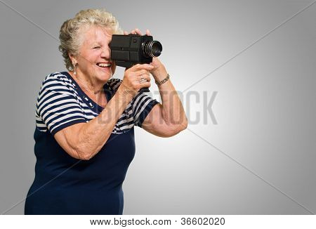 Senior Woman Recording Through Video Camera Isolated Over Gray Background
