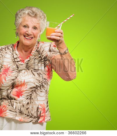 Portrait Of Happy Senior Woman Holding, Orange Juice Glass Isolated Over Gray Background