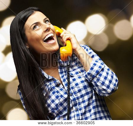 portrait of young woman talking on vintage telephone against a abstract background