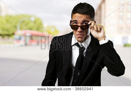 portrait of business man taking off the sunglasses at city