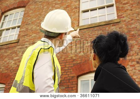 Surveyor Or Builder And Homeowner Looking At A Property