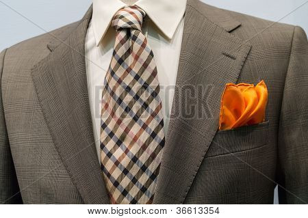 Light Grey Checkered Jacket With Brown Checkered Tie And Orange Handkerchief