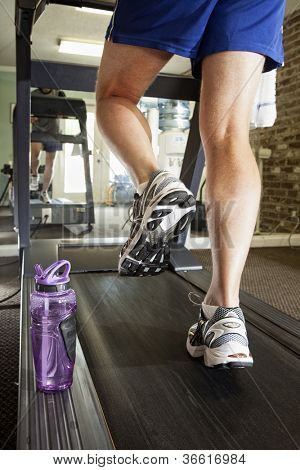 man running on treadmill, focus on shoes
