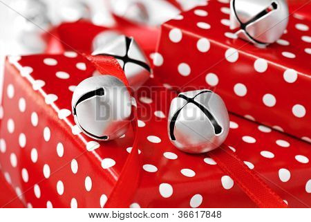 Silver jingle bells with red satin ribbon on gifts wrapped in fun polka dot paper.  Macro with shallow dof.