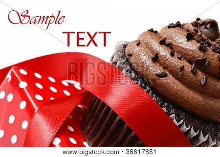 Frosted chocolate fudge cupcake with red satin ribbon and polka dot gift box on white background with copy space.  Macro with shallow dof.
