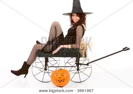 Teen Girl In Halloween Costume On Cart By Pumpkin