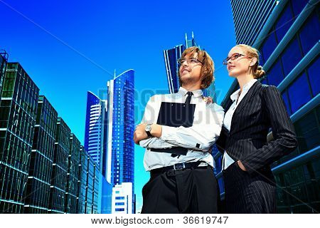 Business people standing in the city and purposefully looking away.