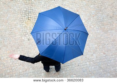 Business man hidden under umbrella and checking if it's raining