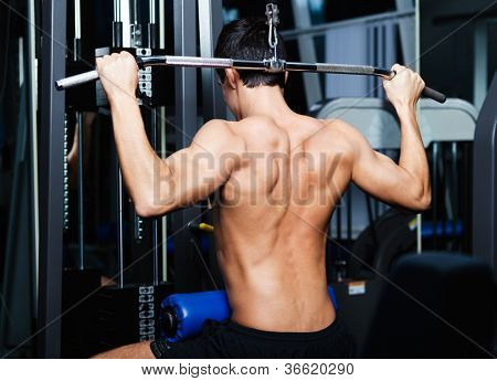 Athletic young man works out on simulator in training gym