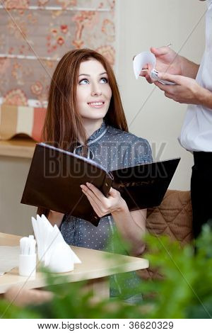 Pretty girl makes an order. The waiter listens to her attentively and white down everything