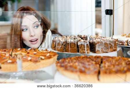 Woman in scarf looking at the bakery glass case full of different pieces of cakes
