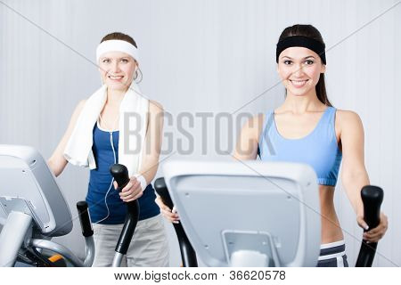 Two young women in sports wear training on training apparatus in gym