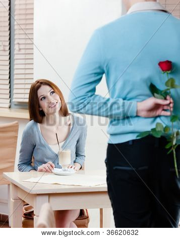 Man keeps red rose behind his back to present it to his girlfriend