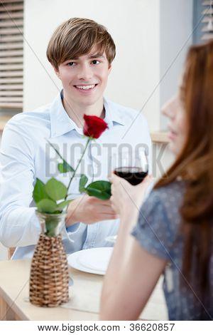 Casal está na casa de café sentado à mesa com o vaso e a rosa escarlate nele
