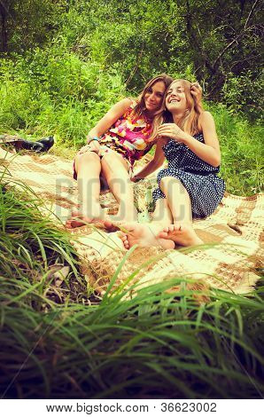 Two Girls Are Sitting On The Grass