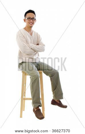 Full body Asian man sitting on a chair over white background