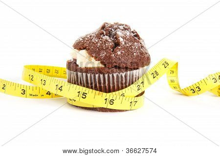 Chocolate Muffin With A Tape Measure Around It On White