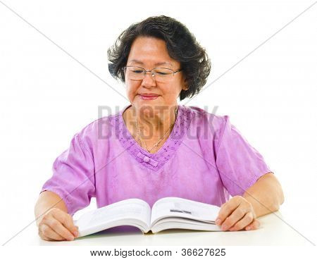 Asian senior woman serious reading book over white background