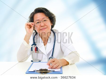 Asian senior female doctor sitting inside hospital room