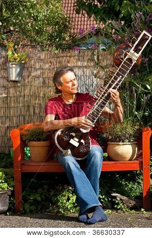 Relaxed Older Man Is Playing A Sitar