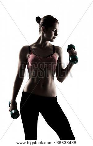 sporty girl doing exercise with dumbbells, silhouette studio shot over white background