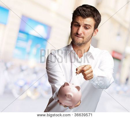 A Businessman Putting A Coin Into A Pink Piggy Bank, Outdoor