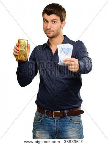 Hombre joven de moneda de tenencia y barra de oro sobre fondo blanco