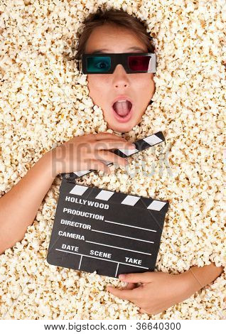 young girl buried in popcorn with movie clapper board