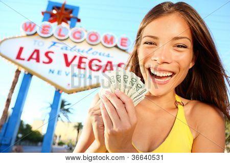 Las Vegas Mädchen aufgeregt halten Geld. Gewinner fröhlich von Welcome to Fabulous Las Vegas Sign. Beauti