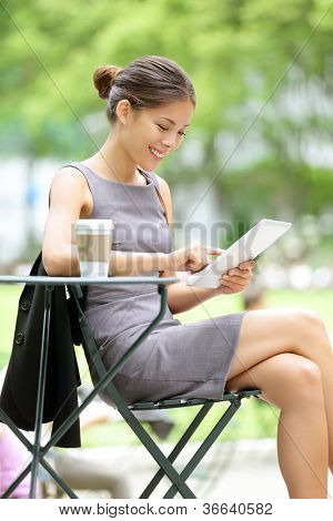 Business woman using tablet on lunch break in city park. Young professional businesswoman sitting at table at cafe. Photo from Bryant Park, New York City, USA.